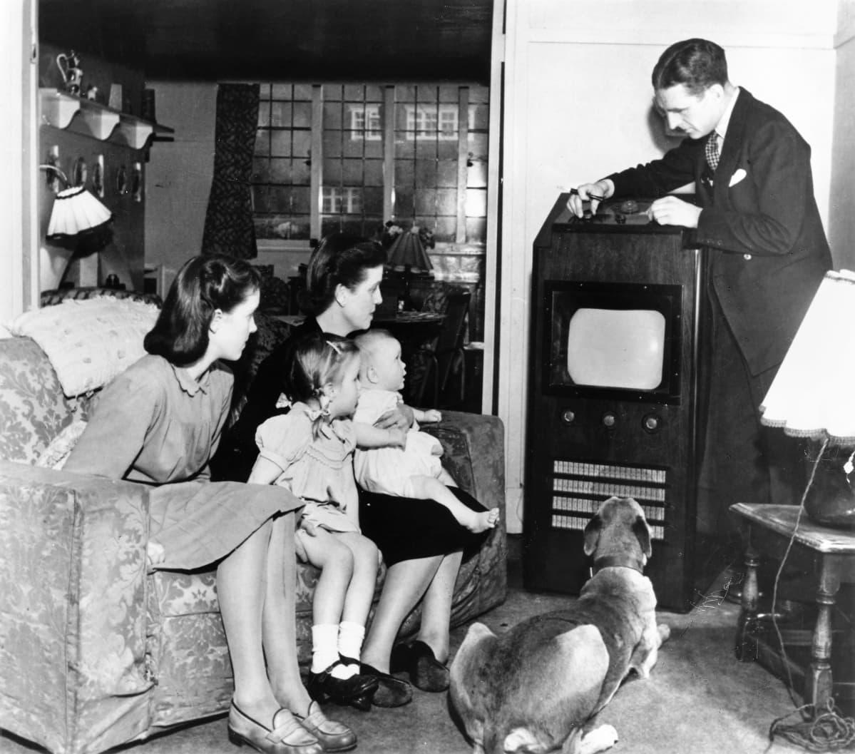 Mustavalkokuvassa perhe katsoo televisiota. Äiti vauva sylissään ja kaksi tytärtä istuu sohvalla, koira makaa lattialla ja perheenisä säätää televisiovastaanotinta.