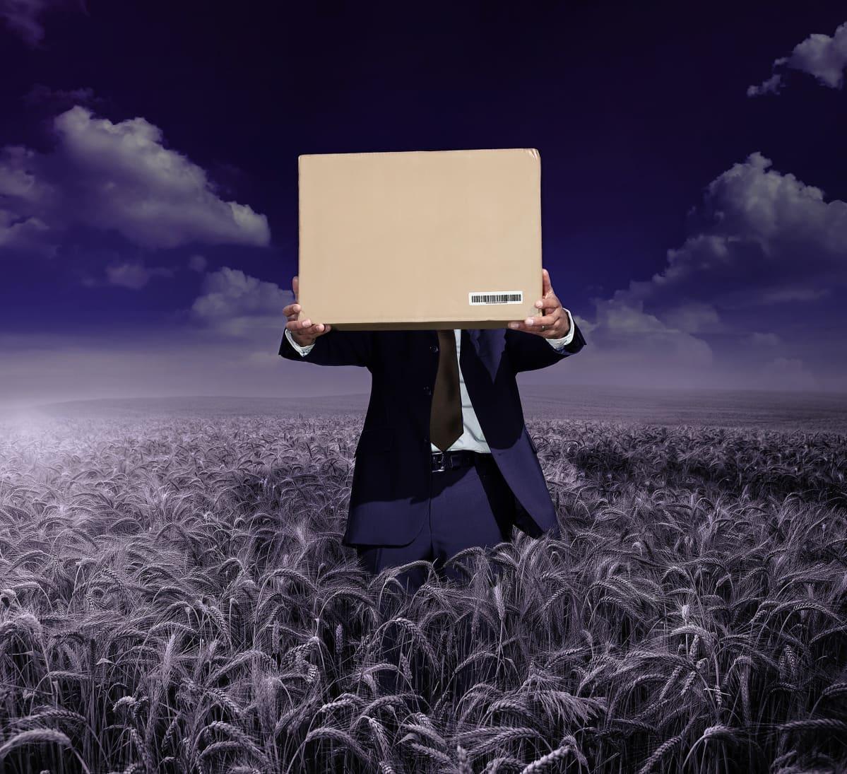 Mies seisoo keskellä peltoa laatikko kädessään