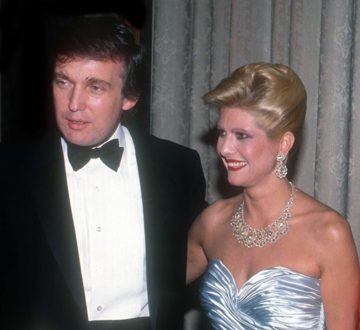 Donald ja Ivana Trump juhla-asuissa. Donaldilla on smokki ja Ivanalla siniharmaa iltapuku ja suuret korut.