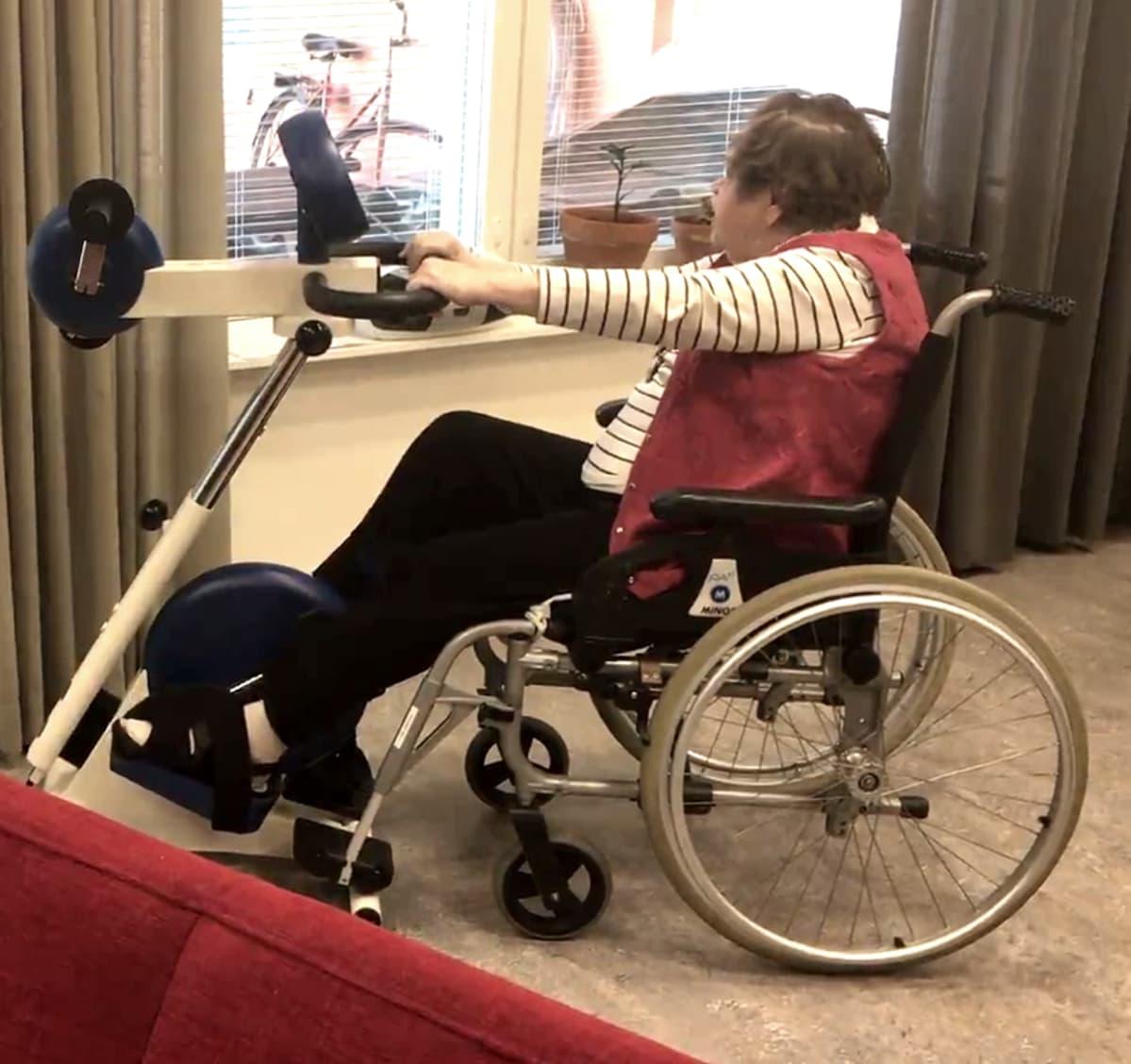 Nainen polkee Motomed-laitetta pyörätuolissa istuen.