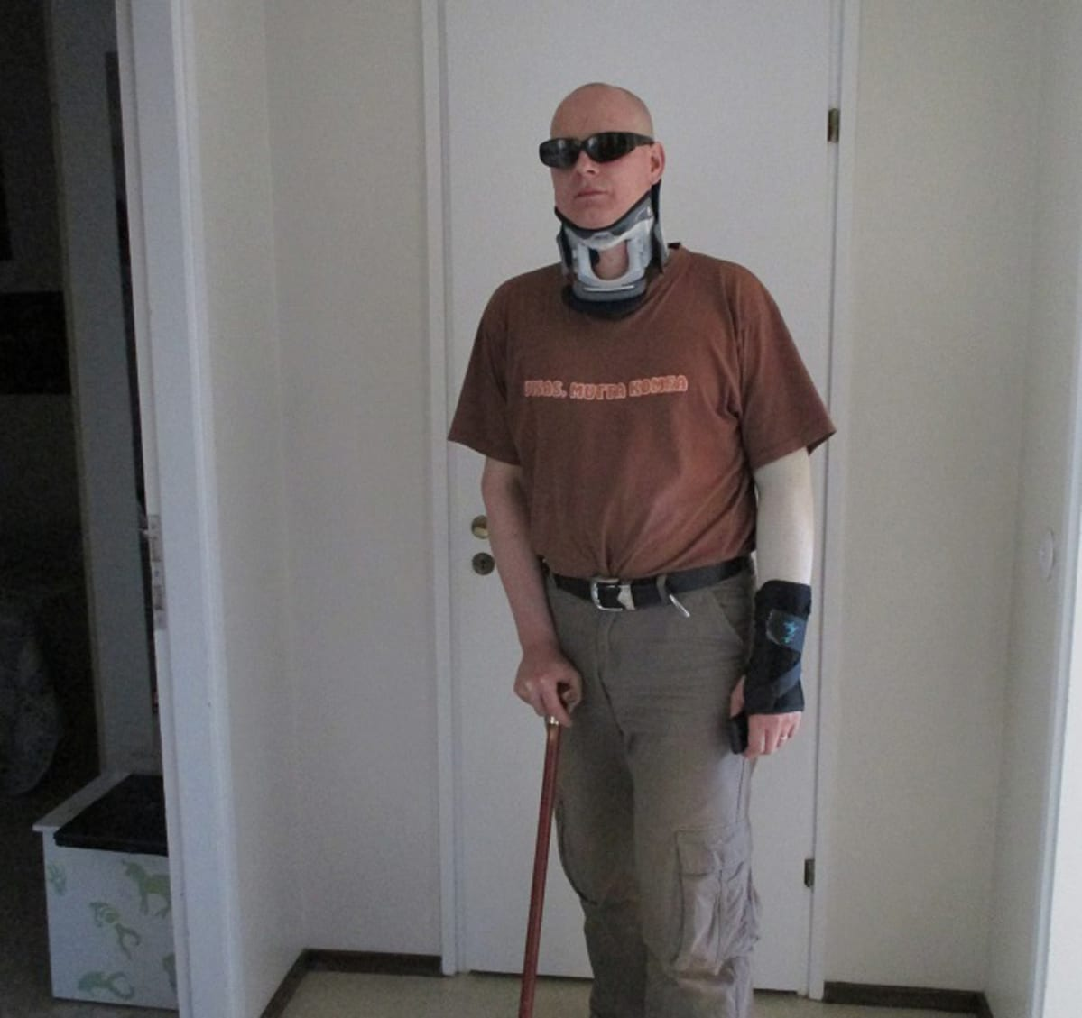 Hans Kallberg nojaa asunnossaan kävelykeppiinsä aurinkolasit päässä