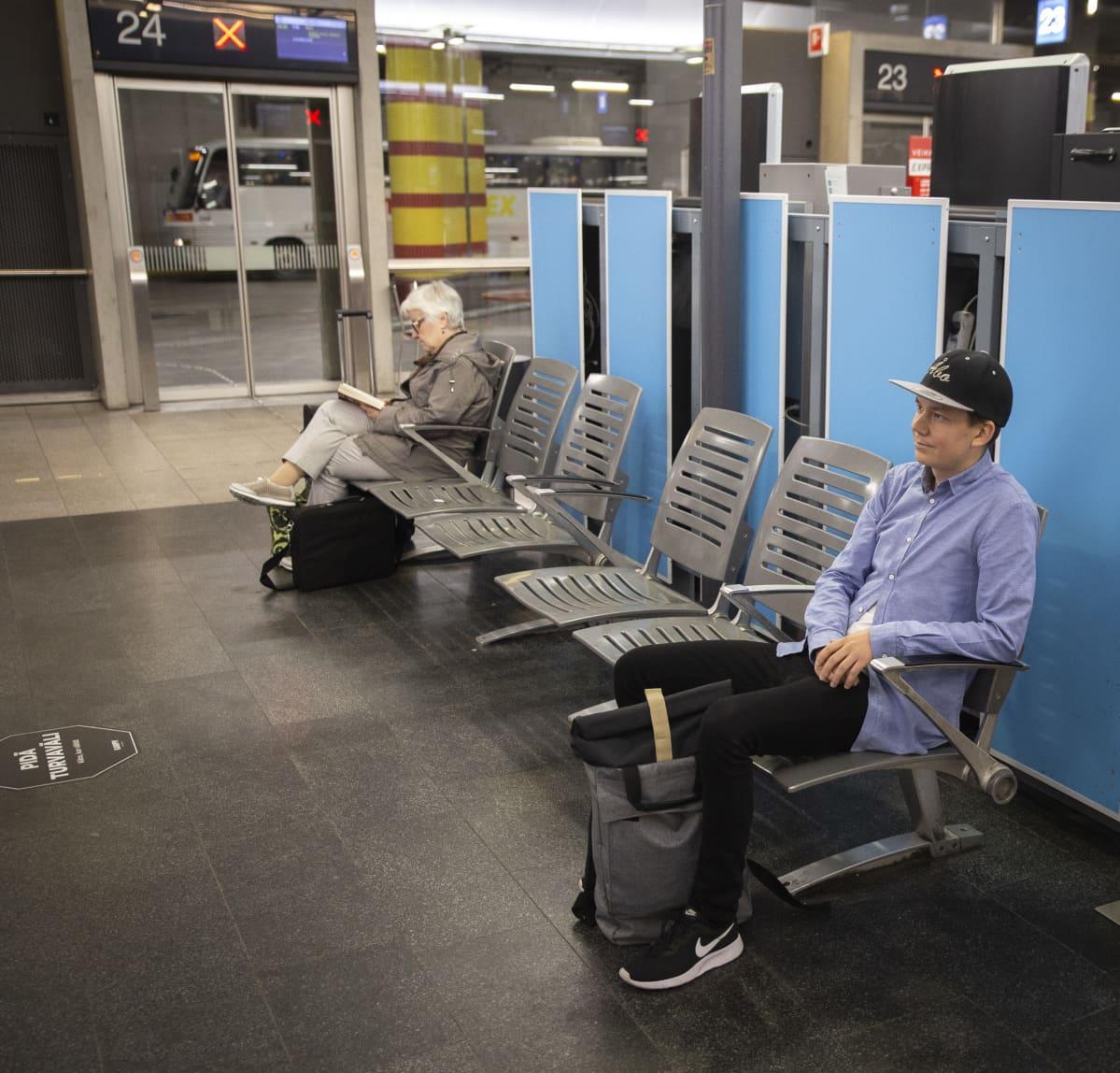 Mies odottaa bussia Kampin linja-autoasemalla.