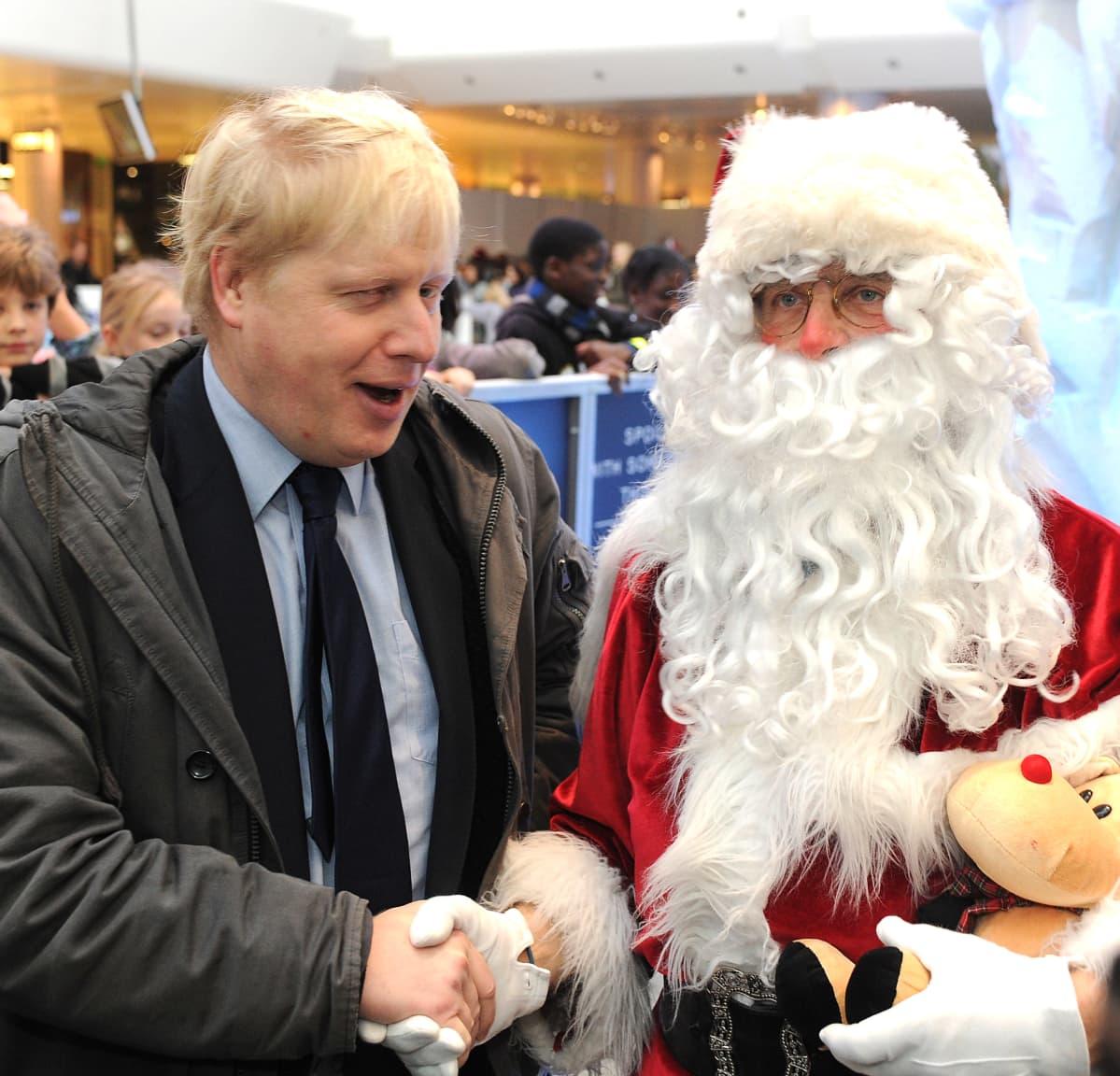 Boris Johnson kättelee joulupukkia.