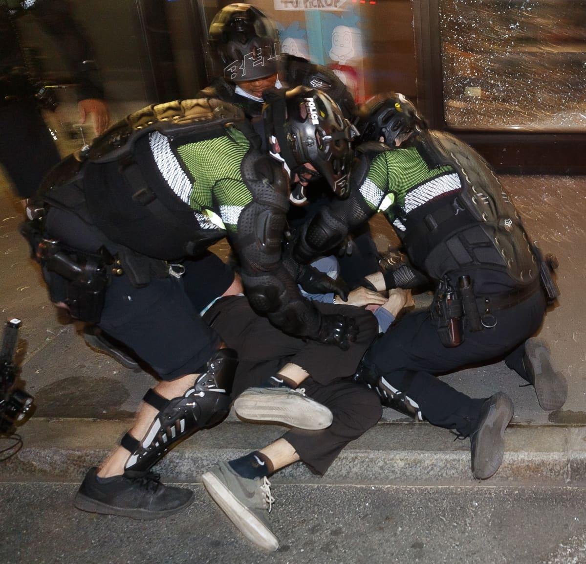 Kaksi poliisia pidättämässä ihmistä.