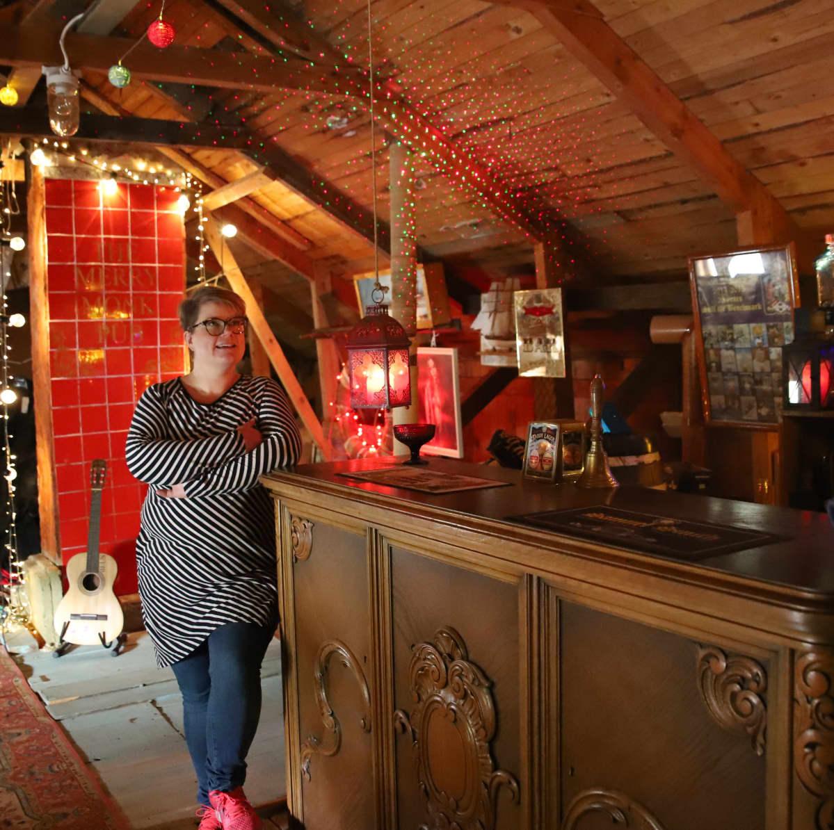Maija Munkki nojailee baaritiskiin kotitalonsa vintillä.