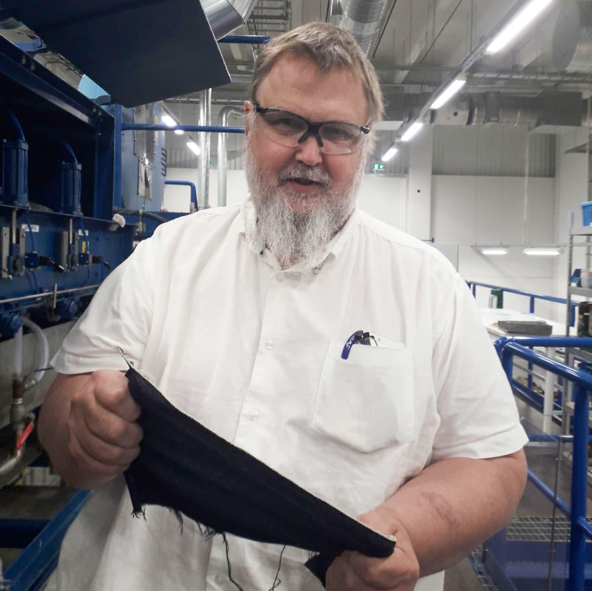 Teknologian kehittämiskeskus VTT:n tutkimusprofessori Ali Harlin esittelee kierrätetystä kuidusta valmistettua farkkukangasta.