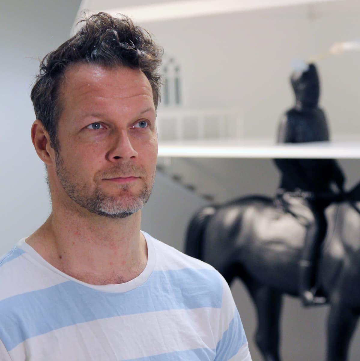 Taiteilija Jani Leinonen Mikkelin taidemuseossa, taustalla Mannerheim-aiheinen teos.