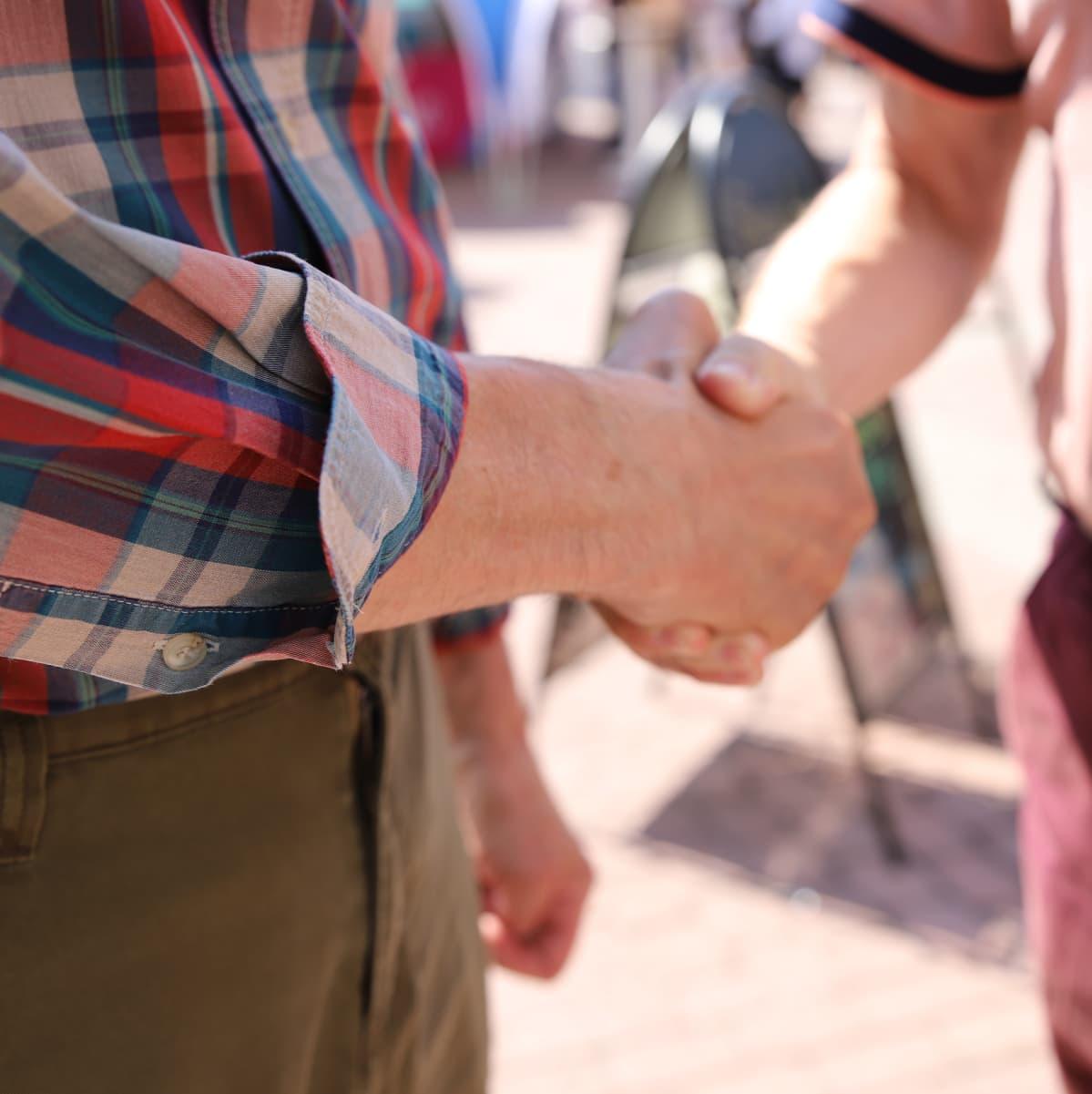 Kaksi mies kättelevät toisiaan