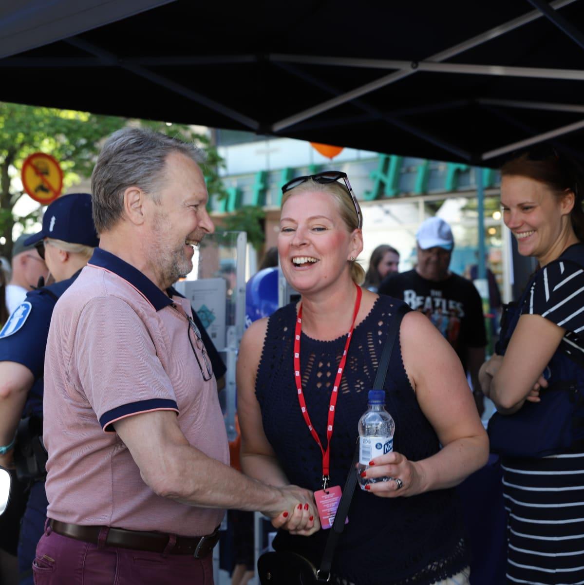 Ilkka Kanerva kättelee vaaleaa naista poliisien teltalla torilla