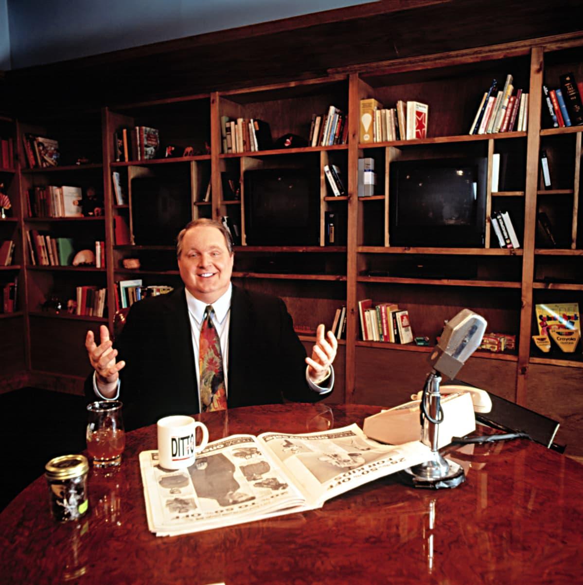 Radiotoimittaja Rush Limbaugh pöydän ääressä jossa radiomikrofoni ja sanomalehti.