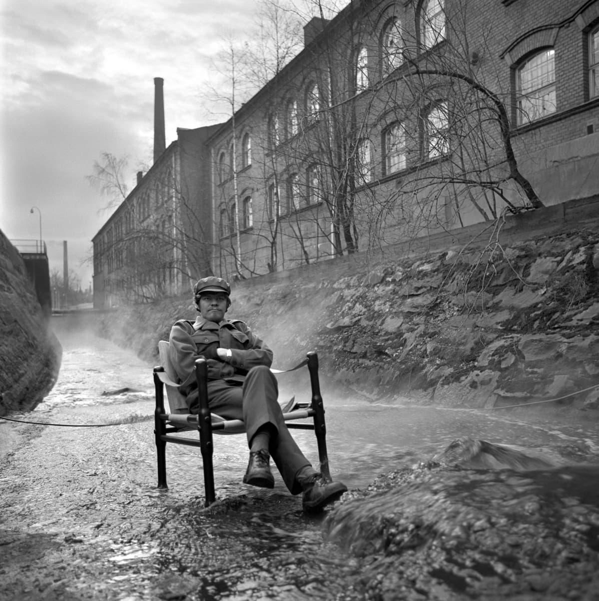 M.A.Numminen istuu tuolilla joka on joessa.