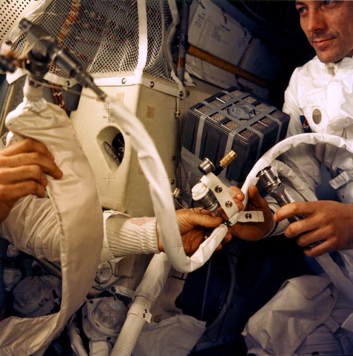 Laitteita ja kaksi astronauttia ahtaassa kuumoduulissa. Vasemmalla olevan astronautin kasvot eivät näy.
