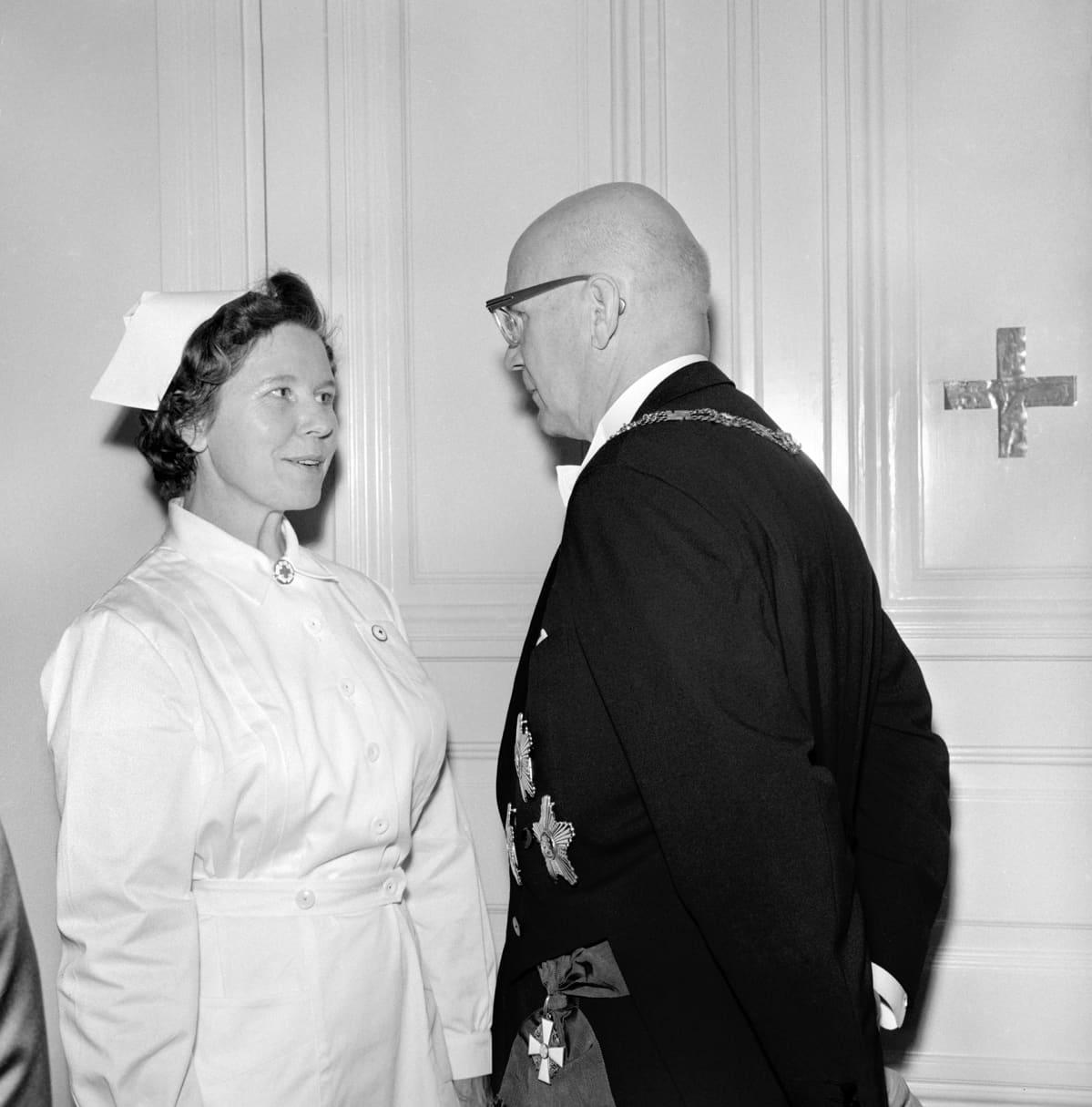 Linnan kutsujen sairaanhoitaja antaa raporttia kutsujen isännälle tasavallan presidentti Urho Kekkoselle 1961.