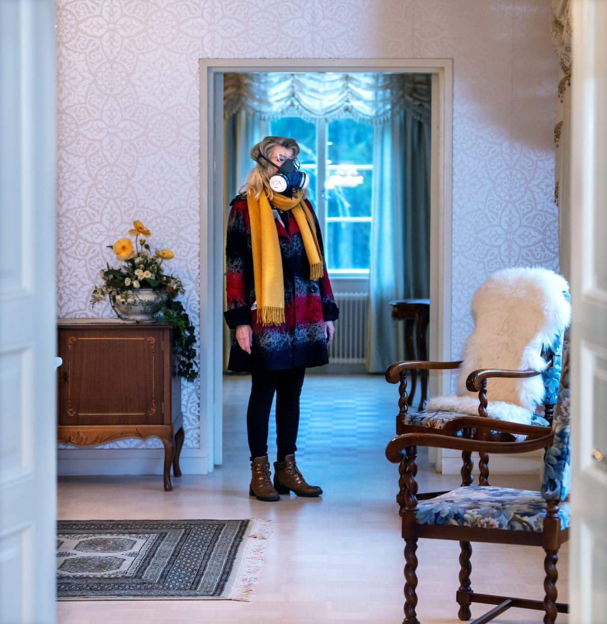 Terttu Aalto seisoo talonsa sisällä hengityssuojain kasvoillaan