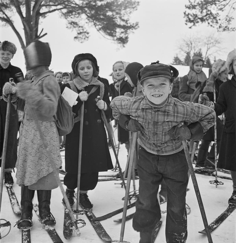 Kymmeniä koululaisia lähdössä hiihtäen kotiin koulusta