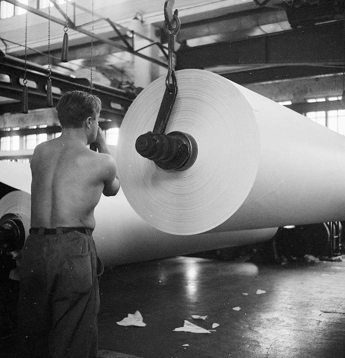 Mies paperikoneen ääressä vuonna 1947