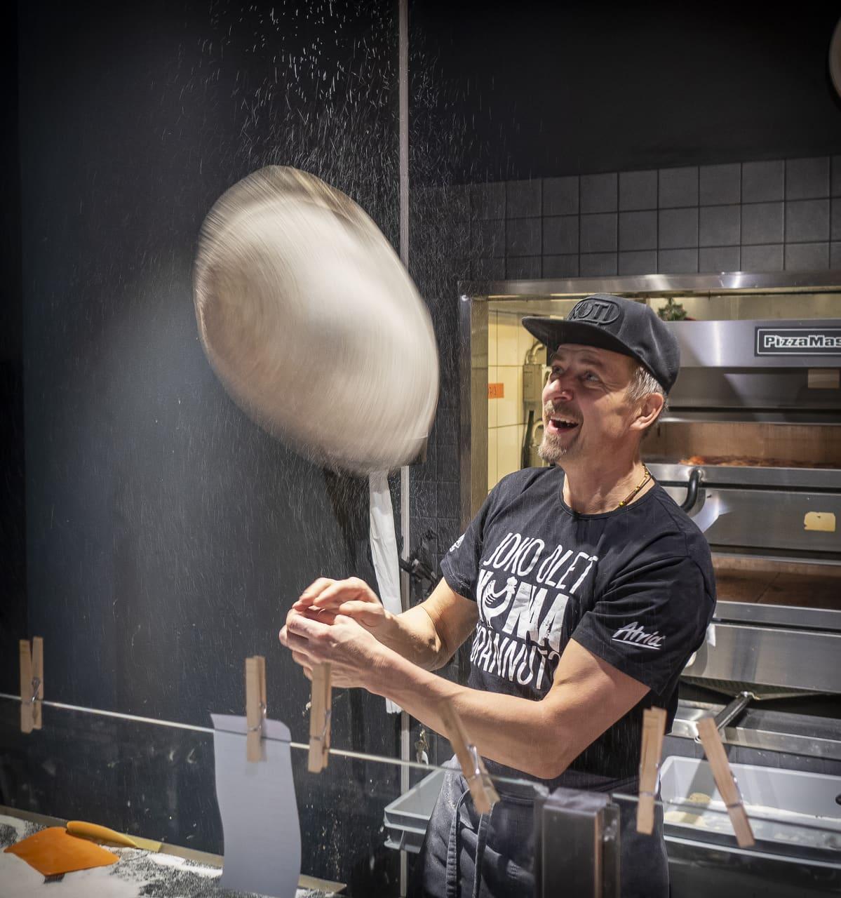 Mies tekee pizzaa.
