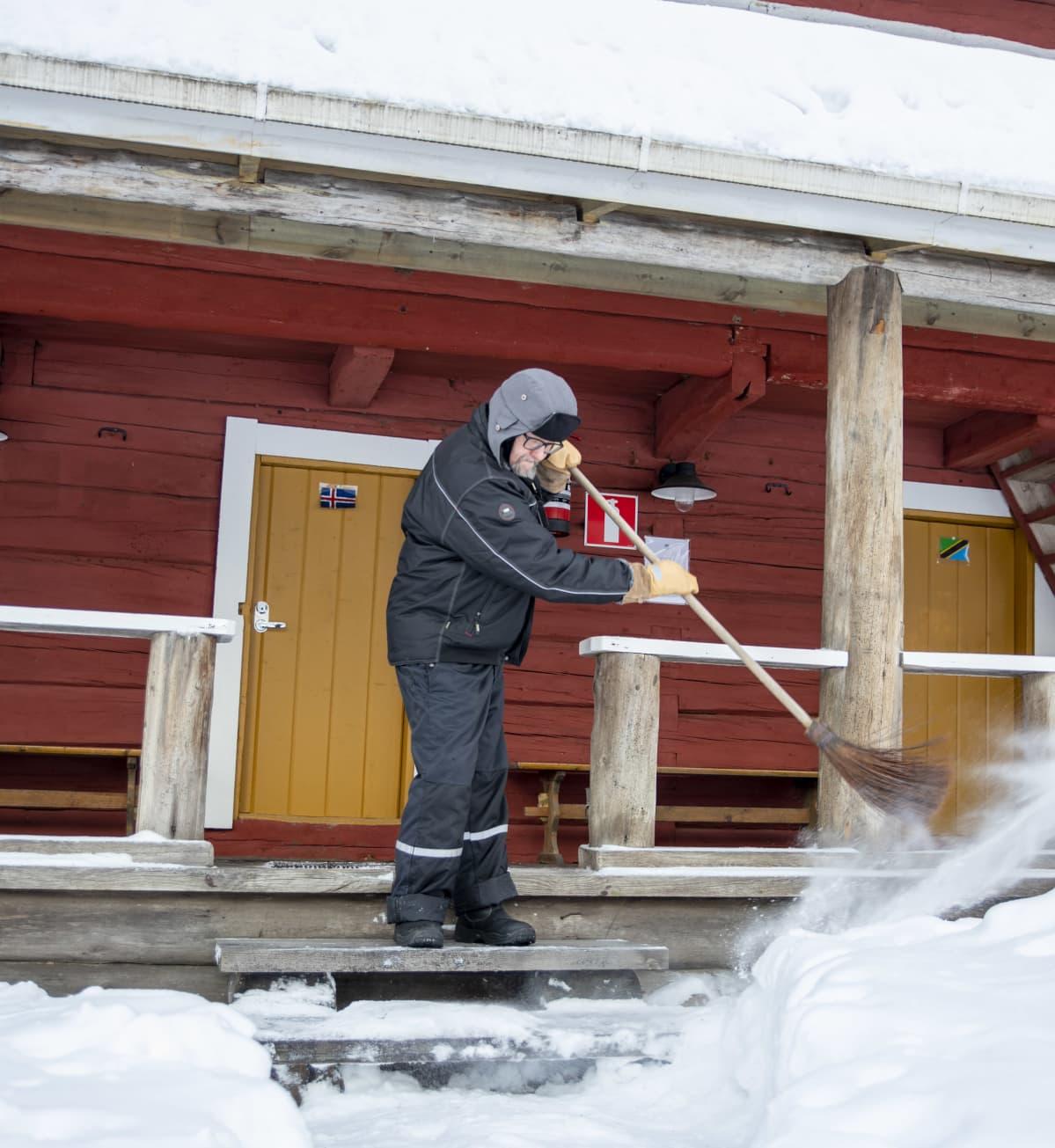 Timo Ruuska siivoamassa lumia aitan rappusilta.