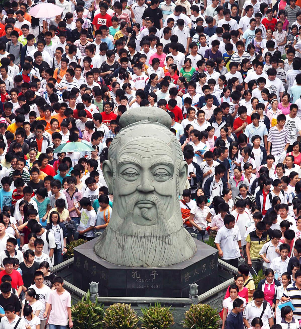 Opiskelijat ympäröivät Kungfutsen patsaan Wuhanissa.