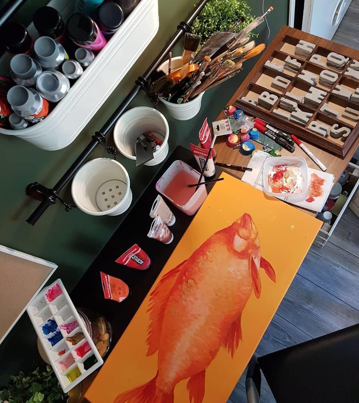 Oranssi kalataulu ja taiteilijantarvikkeita