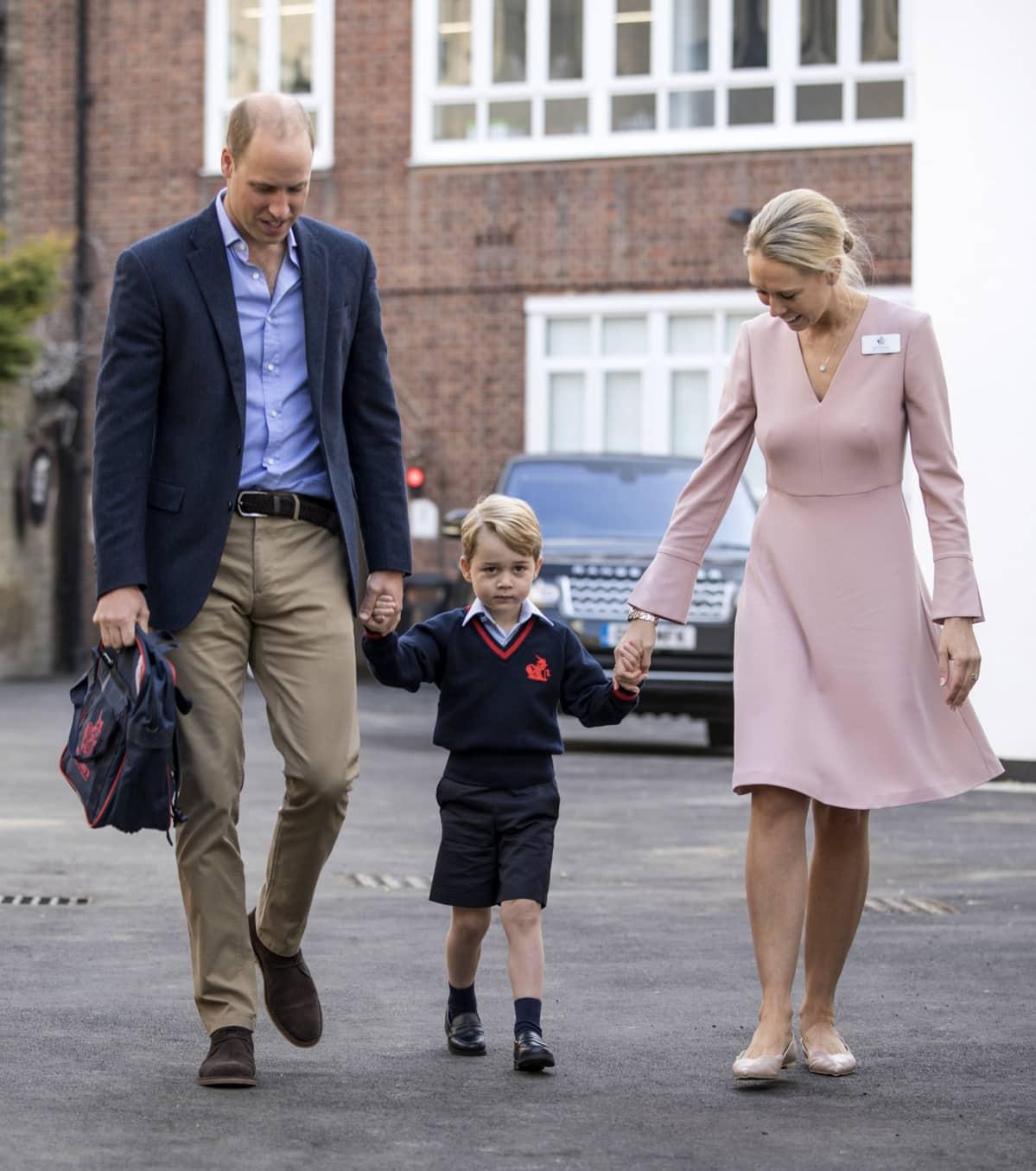 Prinssi George kävelemässä käsi kädessä isänsä prinssi Williamin ja alakoulunsa rehtorin Helen Haslemin kanssa.