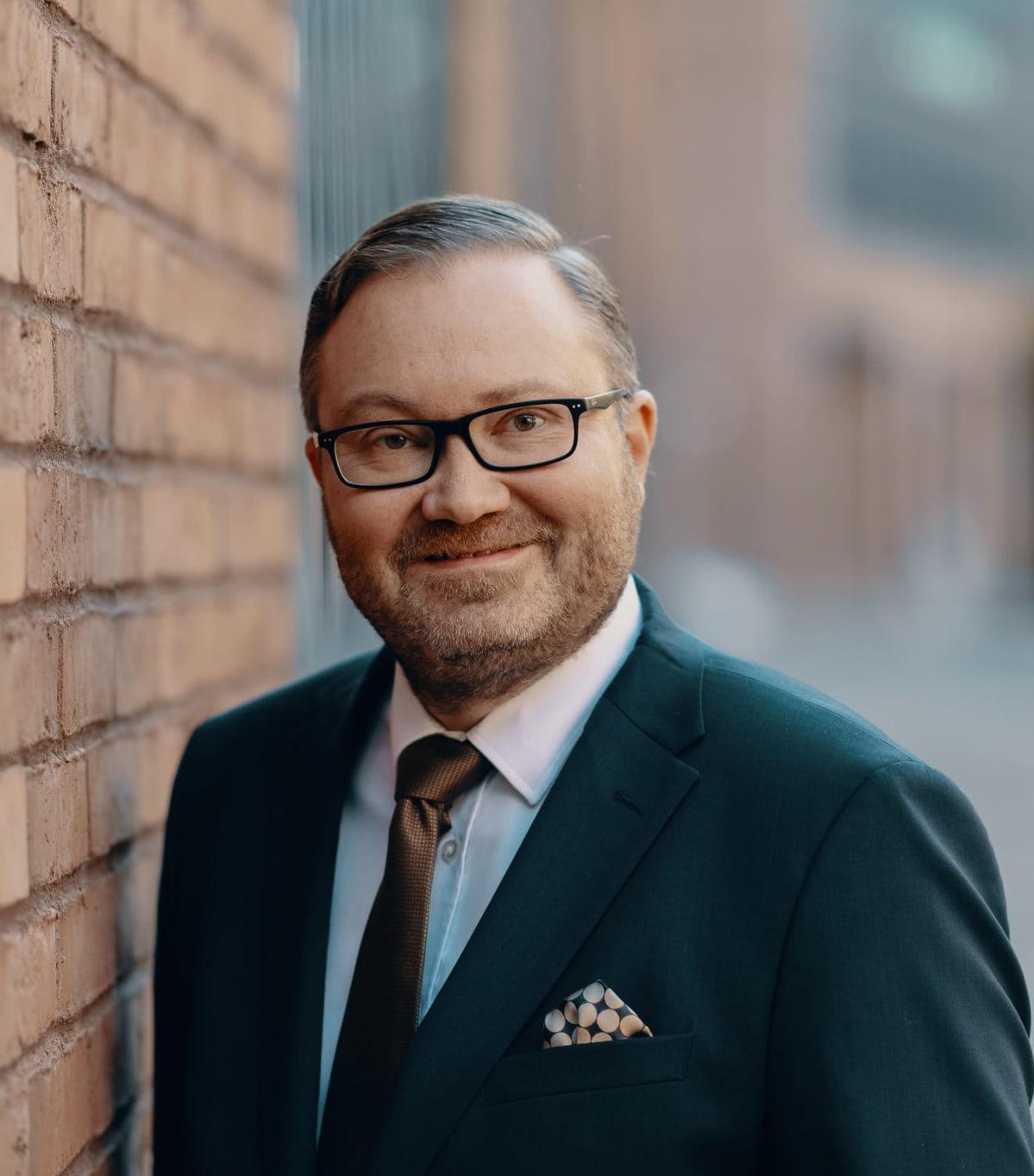 Digi- ja väestötietoviraston pääjohtaja Janne Viskari sinisessä puvussa hymyilee kuvaajalle.