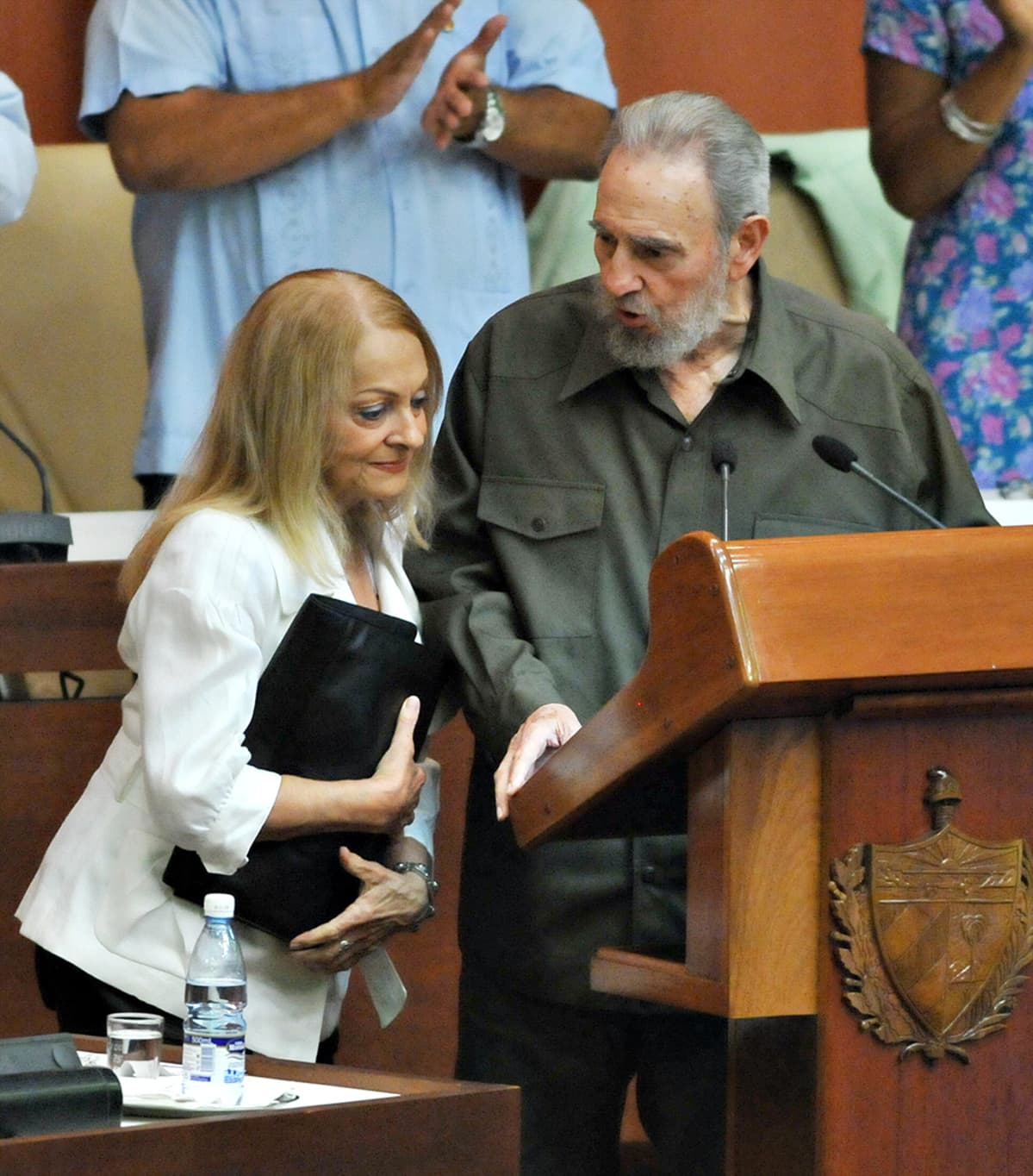 Fidel Castro seisoo puhujakorokkeella Kuuban parlamentissa, vierellään vaimo Dalia Soto de Valle.