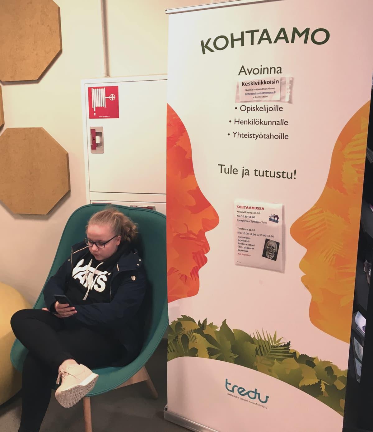Tyttö selaa kännykkää tuolilla istuen. Vieressä on iso juliste, jossa lukee Kohtaamo, ja alla pienemmällä tietoa toiminnasta.