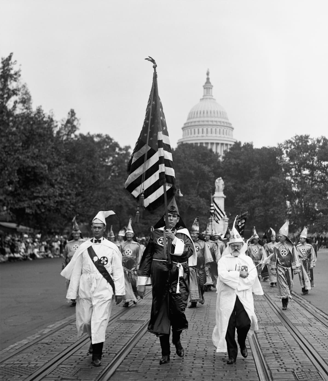 Ku Klux Klanin kaapuihin pukeutuneet miehet marssivat pitkin katua. Taustalla näkyy kongressin rakennus Capitol Hillillä.