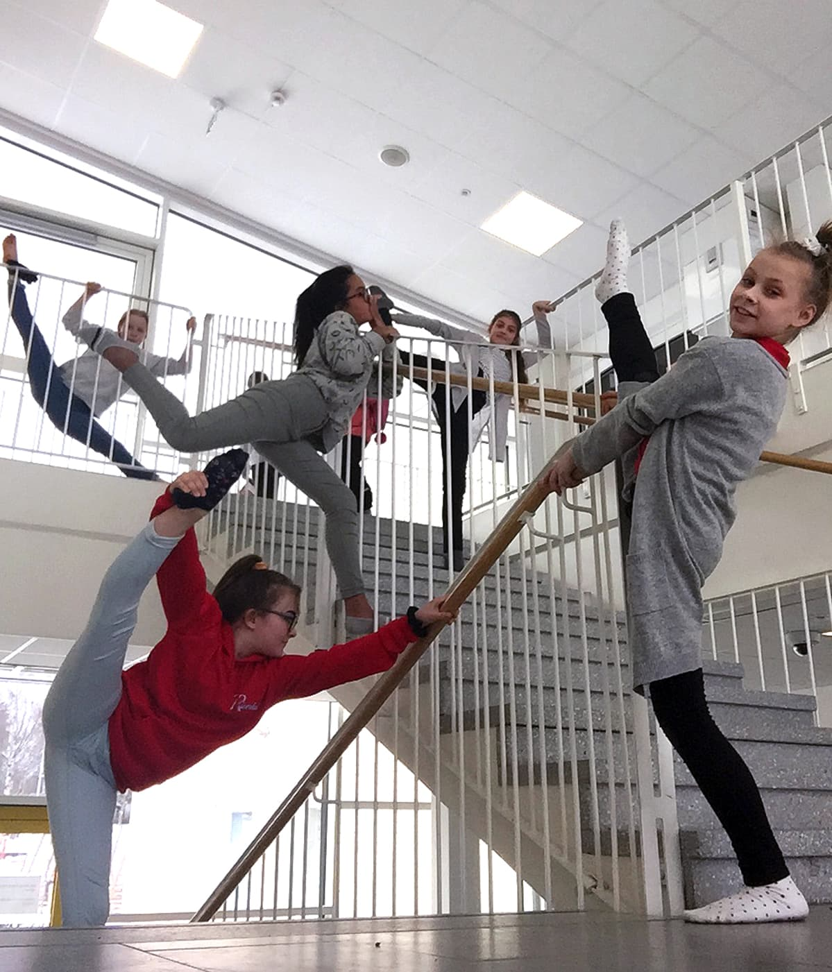 Joukko lapsia venyttelee portaissa.