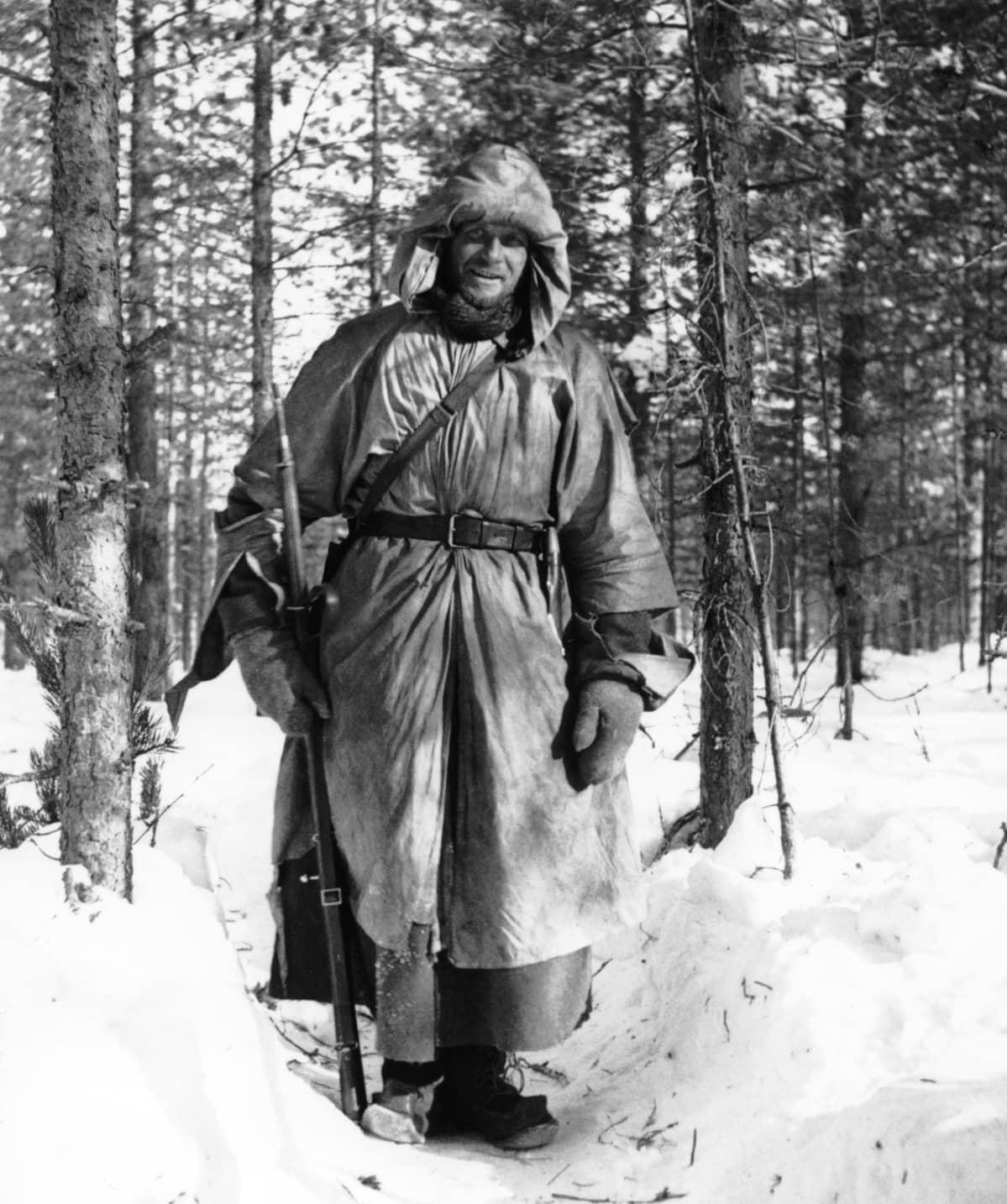 Sotilas seisoo talviasussa ase kädessä lumihangessa.