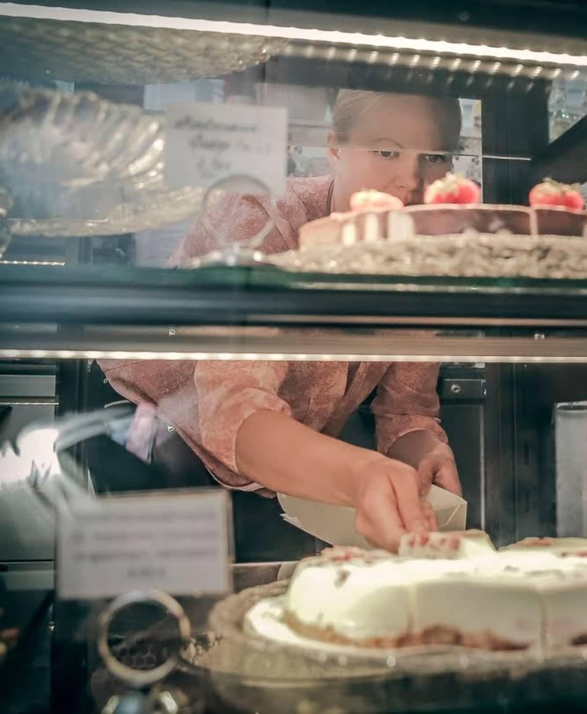 Miriam Laitinen nostamassa kakun palaa laatikkoon.