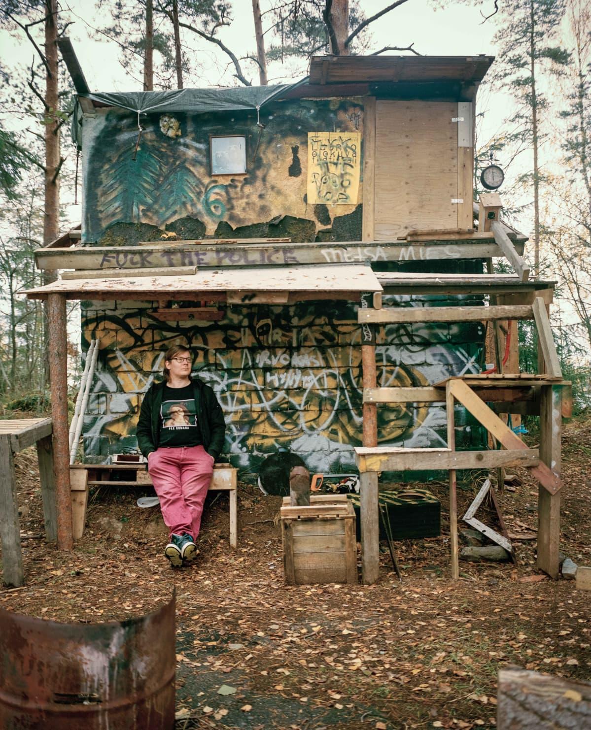 Mies nojaa graffiteilla maalattuun pieneen rakennukseen metsässä.