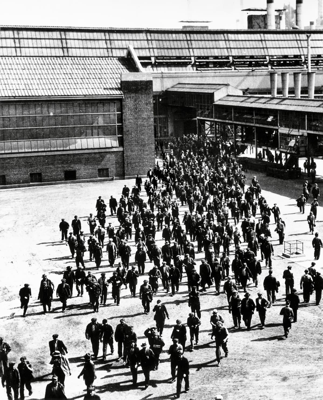 Mustavalkokuva. Suuri joukko työläisiä purkautuu tehtaan ovista laajalle pihalle.