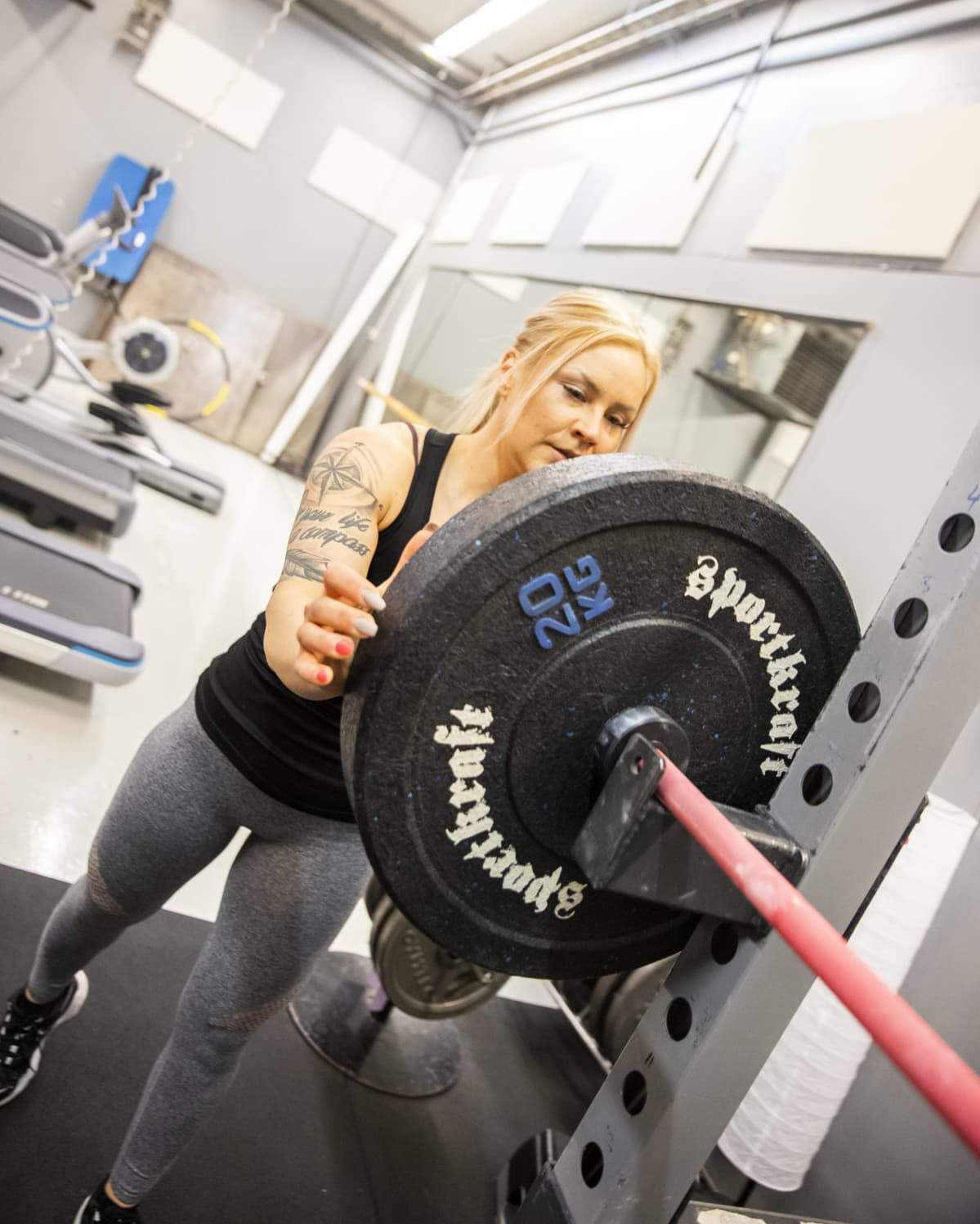 Body fitness-urheilija Tiia Takala kuntosalilla.