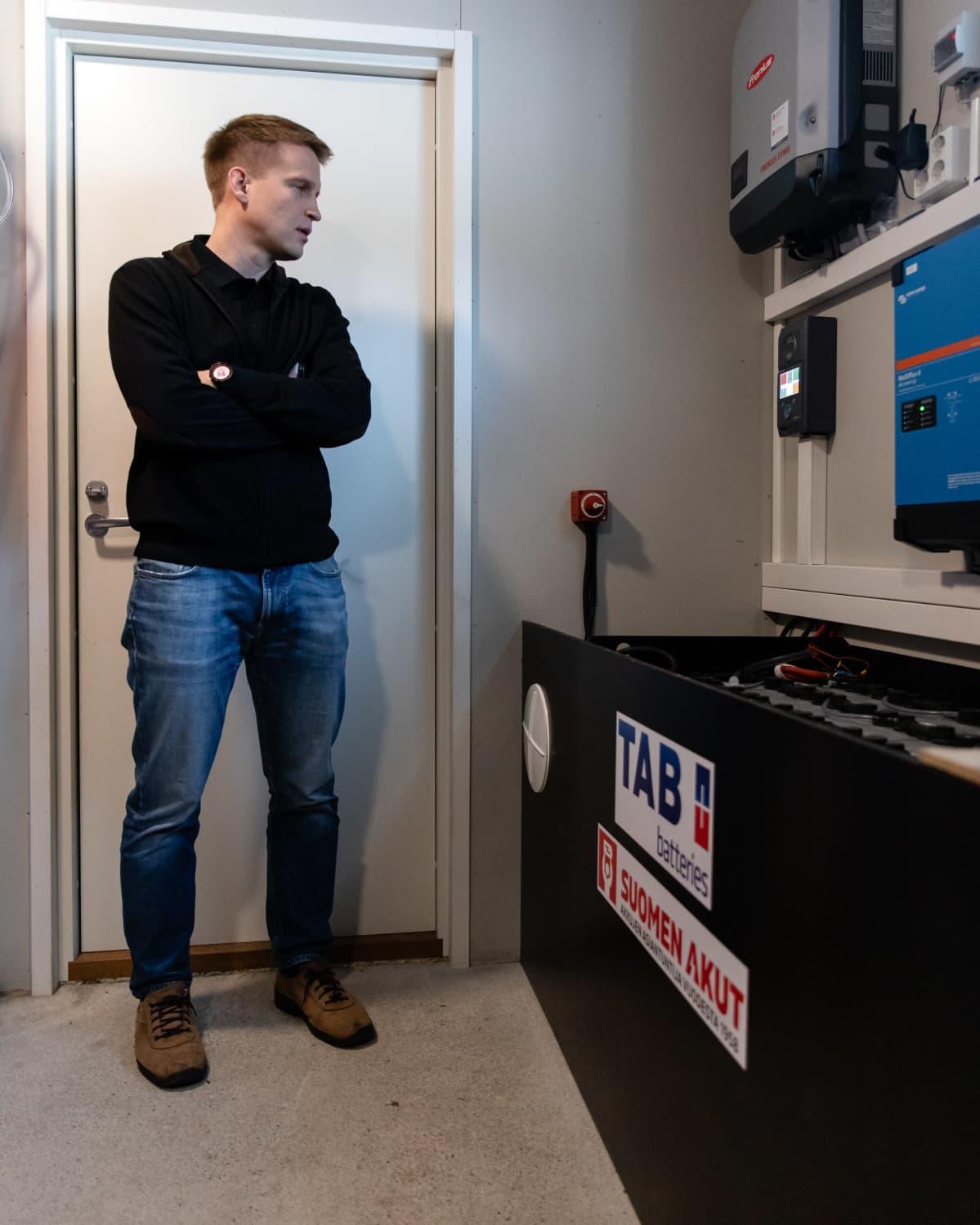 Jussi Tuunanen seisoo aurinkovoimalan akkujen vieressä varastotilassa.