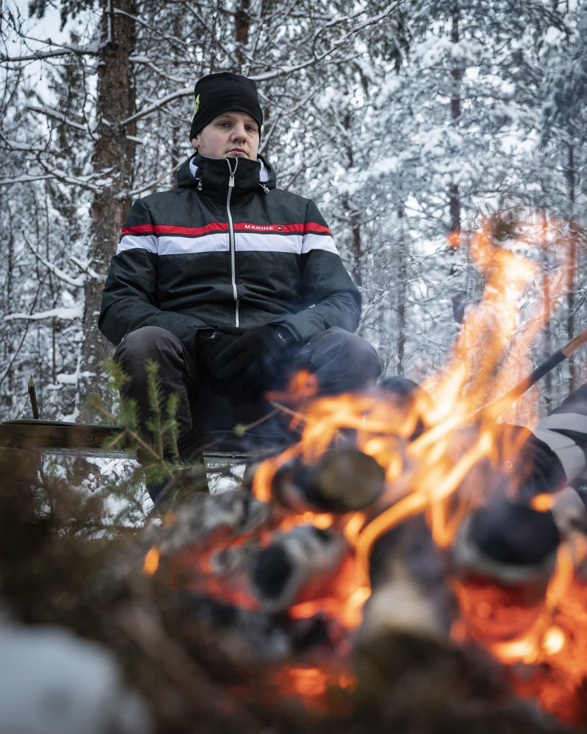 Mikko Karhukorpi istuu nuotion ääressä metsässä.