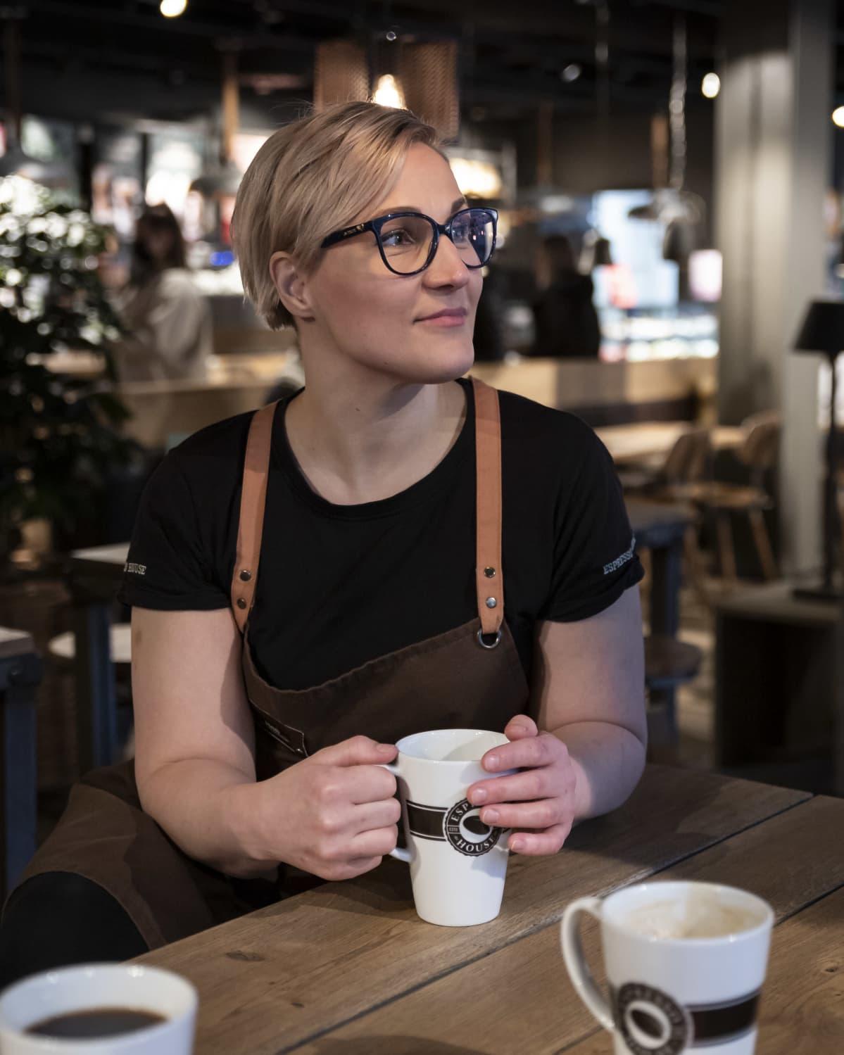 Nainen istuu kahvikuppia pidellen kahvilassa.