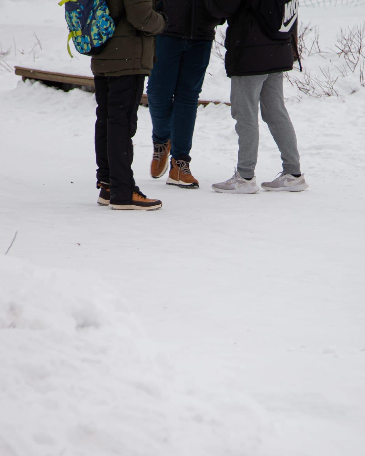 Anonyymeja poikia seisomassa Lauritsalan koulun lumisella pihamaalla.