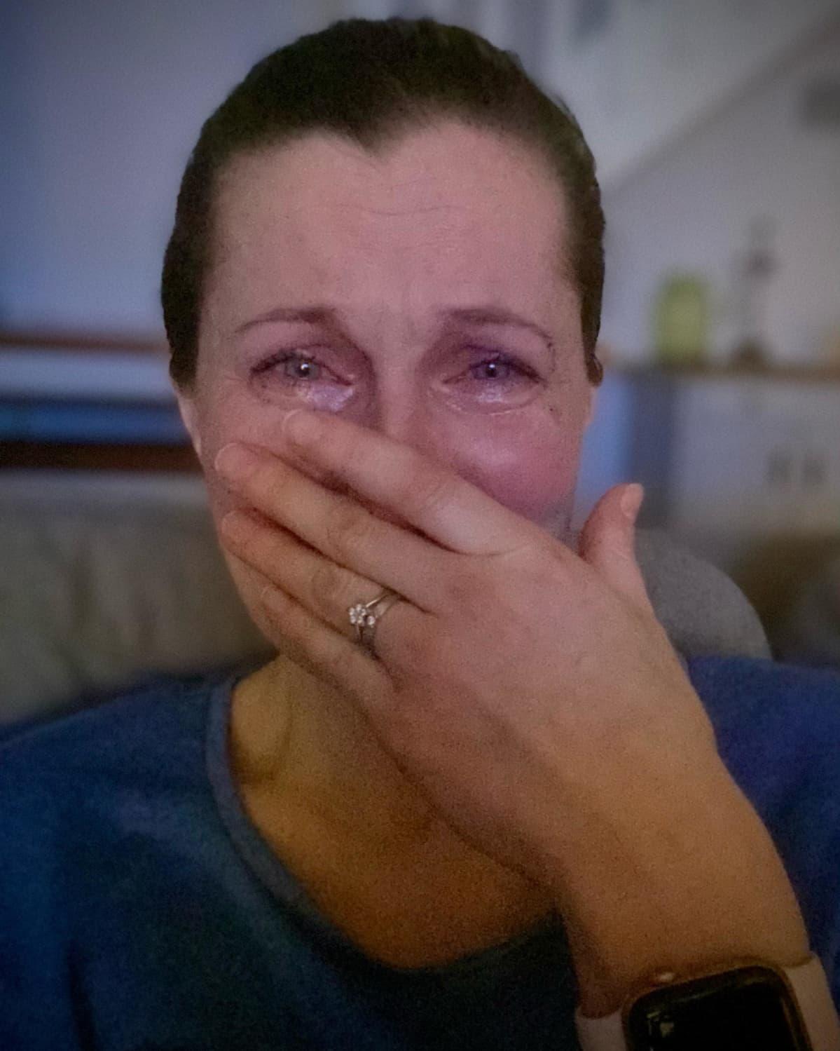 Jenni Höjerin itse ottama kasvokuva, jossa hän itkee käsi suun edessä.