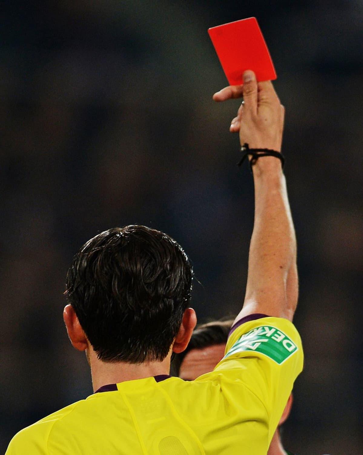 Tuomari näyttää punaista korttia jalkapallokentällä.