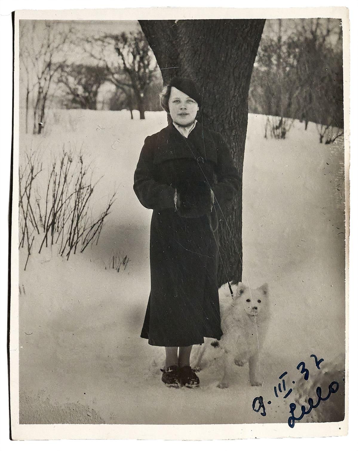 Nainen ja koira talvella puun alla.