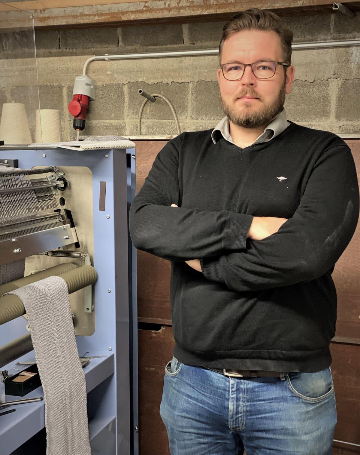 Tehtaanjohtaja Juha Haapasaari seisoo neulekoneen vieressä