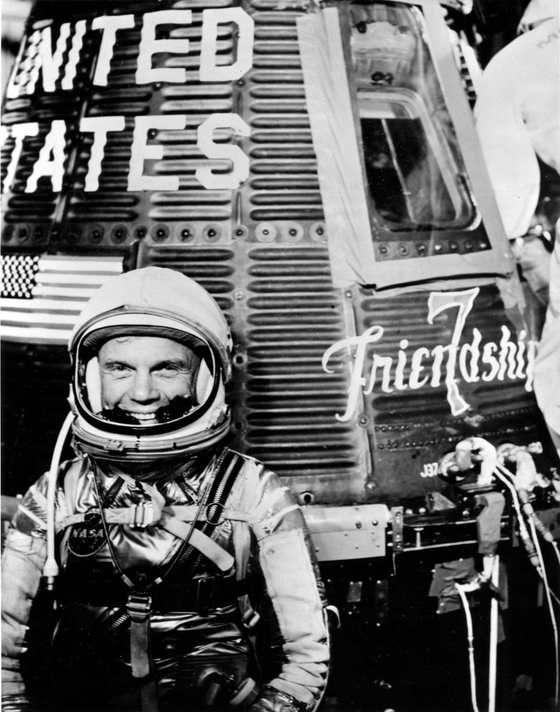 Mustavalkoinen kuva, John Glenn hymyilee avaruskypärä päässään.