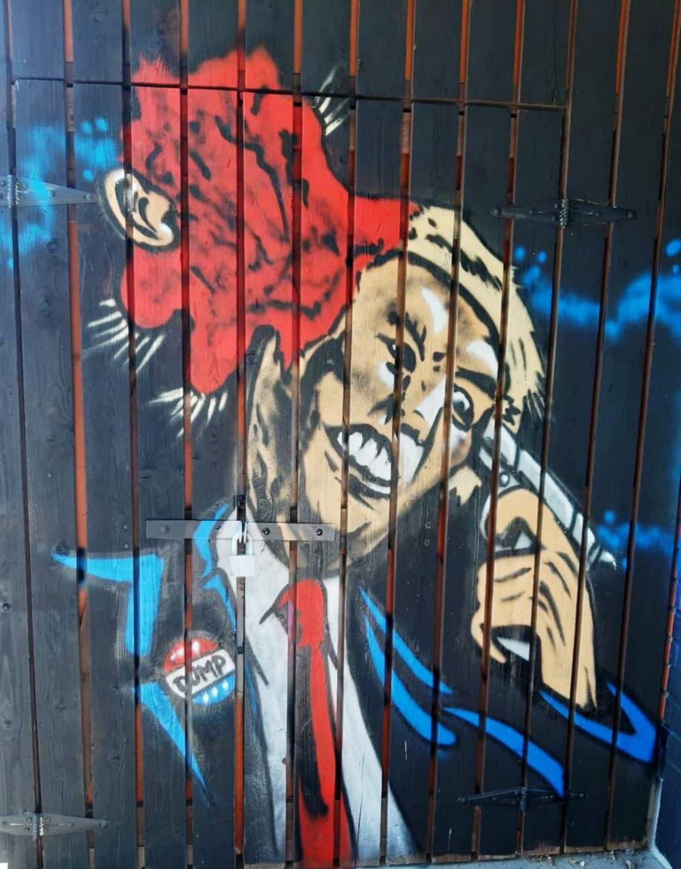 Seinään tehty katutaideteos, jossa presidentti Donald Trump ampuu itseään päähän