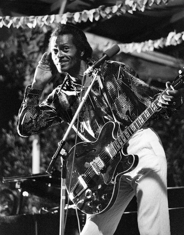 Chuck Berry kuuntelee yleisön äännehdintää oikea käsi oikealla korvallaan ja katsoo lempeän leikkimielisesti valokuvaajaa kohti.