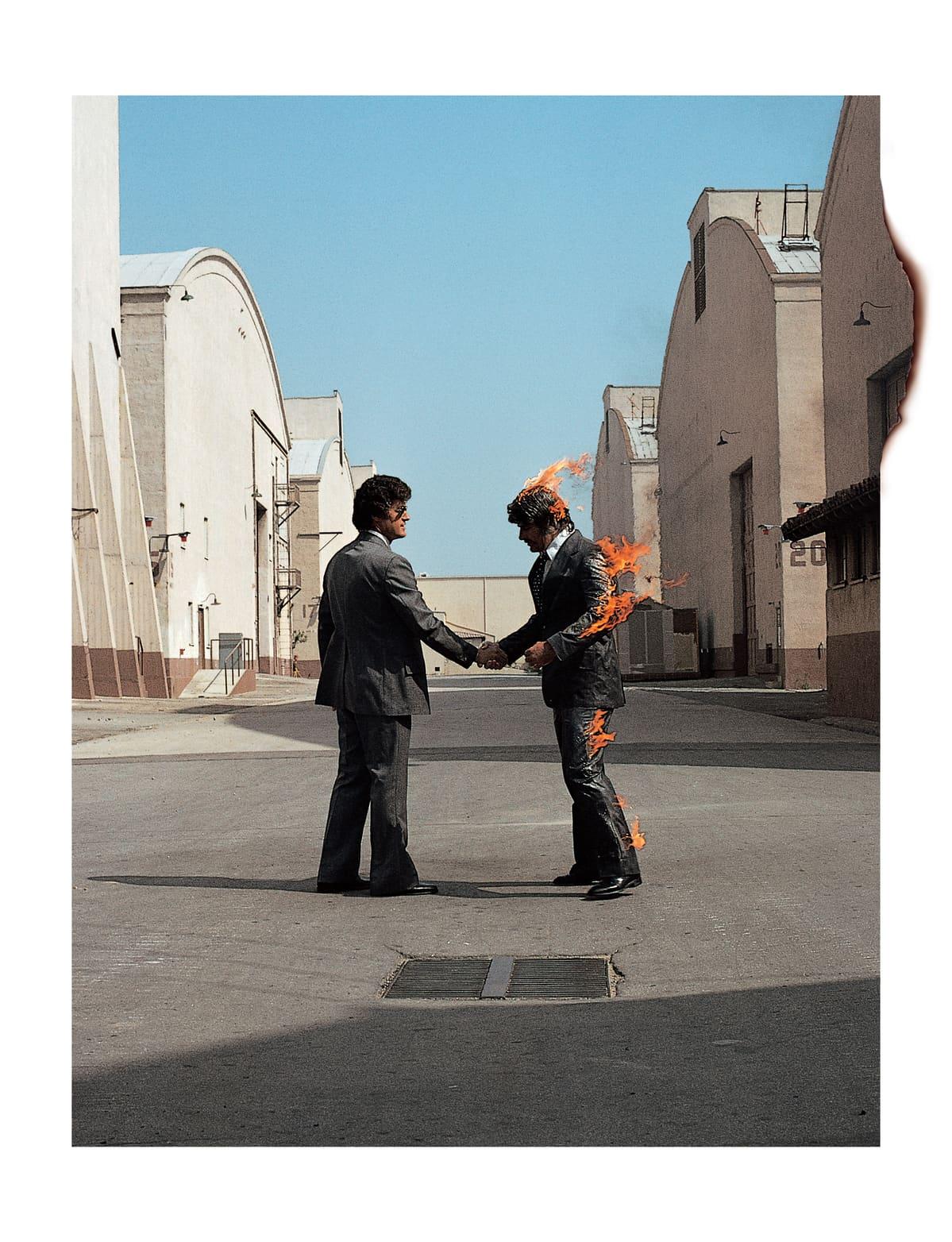 kaksi miestä kättelee, toisen puku on tulessa