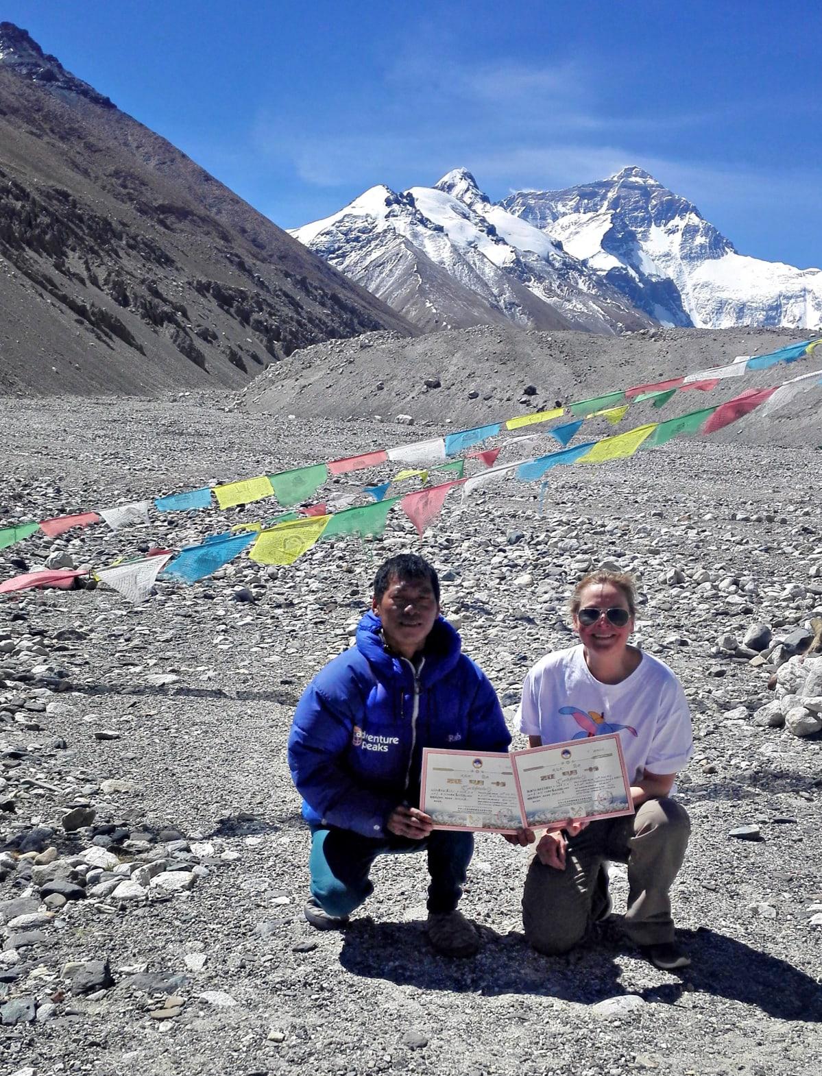 Paula Strengell (oikealla) vieressään sherpa Pemba. Molemmilla on todistukset kädessä. Taustalla näkyy Mount Everestin huippu.