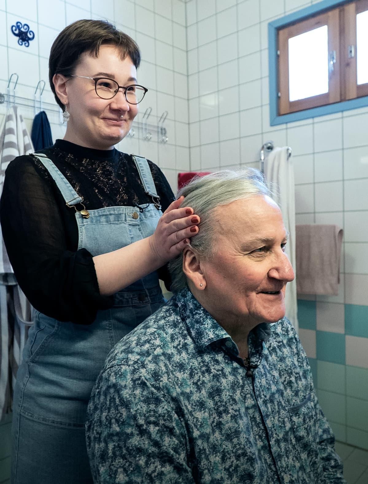 tytär laittaa isänsä hiuksia