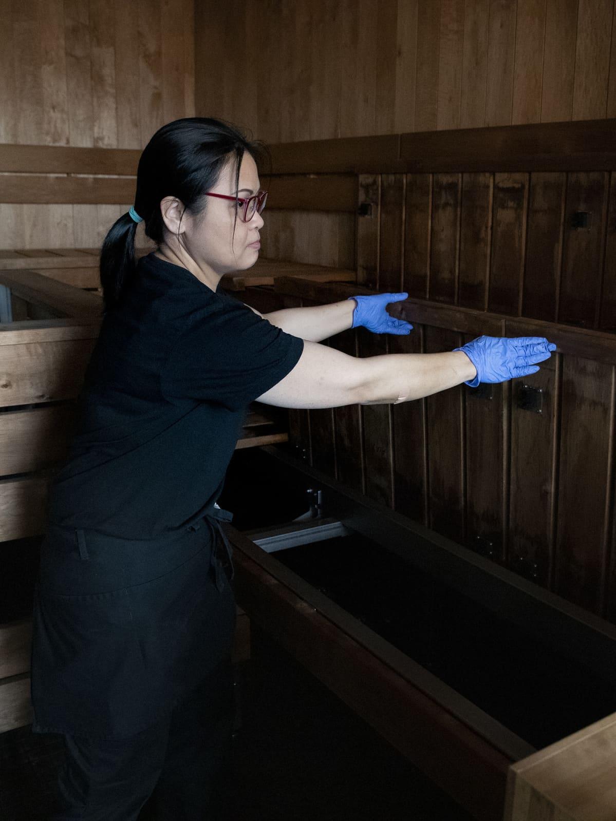 Siivooja nostaa hotellin saunan lauteet ylös pestäkseen lauteiden alapinnat.